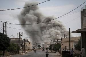 Röken ligger tät över en by i norra Syrien efter en flygräd.