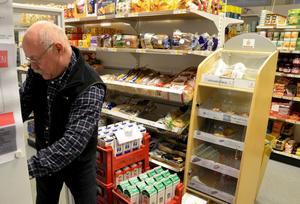 Tar emot varor. Jan Forslund tar emot och plockar upp mejerivaror i affären i Järnboås.