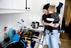 Jenny Einarsson och tvåårige Albin värmer vatten på en dålig spis för att kunna diska.