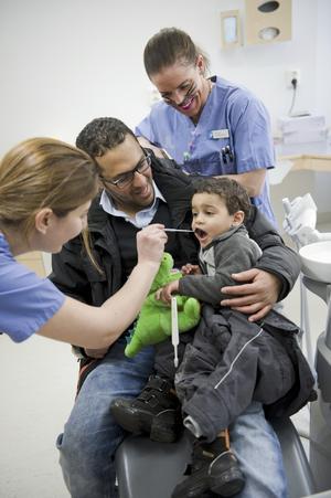 Gapar stort. Saeed Abdu, 3, sitter i pappa Arefs knä och låter sig bli undersökt. Det är tryggt, dessutom har han en drake som stöd.