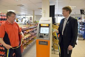 Ulf Jönsson vid Särnas egen penningmaskin sedan den officiellt invigts med hjälp av kommunfullmäktiges vice ordförande Åke Näslund.