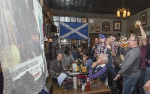 Skotska pubbesökare följer torsdagens folkomröstning på en projicerad jättebild av direktsänd tv.