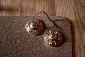 Klockorna heter Tingshas, de slås mot varandra och skapar ett klart vibrerande ljud. Dessa används inom den buddistiska traditionen innan och efter meditation.