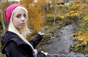 Forsande. Victoria Ögren fångar ljudet från det rinnande vattnet med hjälp av sin mobil. BILD: BIRGITTA SKOGLUND