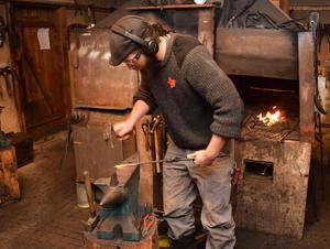 Talon Wilson tillverkar en krok i smedjan.