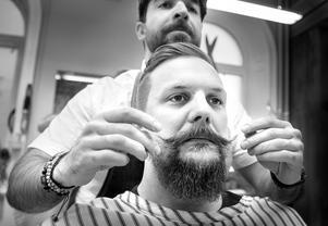 Tobias Andersson får sitt skägg friserat av Omad.