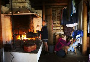 På Östnårbuan är frukosten precis avklarad och Rasmus Olsson, åtta år, försöker dra fukten ur kroppen vid eldstaden. Ingrid Jeppesen, nio år, kelar med gårdskatten.