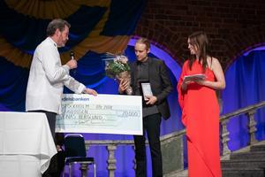 Jonas Berglund tar emot utmärkelsen av Stefan Fritzdorf, ordförande för Stockholms Handelsförening.