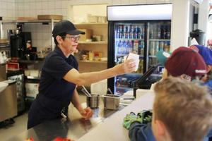 Gun-Lis Bergman serverar den första hamburgaren till Theo Gransten.