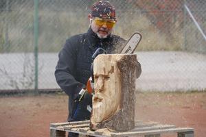 Staffan Hanning gör en luffarbrasa med hjälp av en motorsåg och en trästubbe.