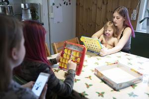 Hilma spelar sällskapsspel med lillasyster Minnah och storasyster Tove.