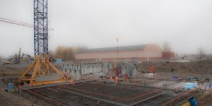 Den stora byggkranen används för alla transporter på arbetsplatsen och når 80 meter åt alla håll. Där kranen står kommer vattenrutschkanan att anläggas. Männen bland armeringsjärnen närmast står där bassängens djupaste ände kommer att ligga.