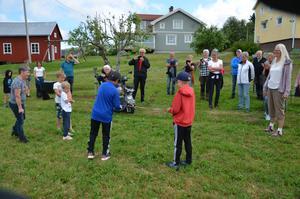 Invigning av lekytan mitt i byn. Vi ser killar som håller i bandet och en som klipper och i bakgrunden har vi både vuxna och barn som hejar på. Foto: Bertil Westin