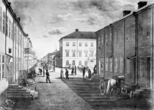 Drottninggatan med Enneska huset, sedermera Stadshuset i centrum av bilden. Posten till vänster. Bild: G Reimers, 1860-talet.