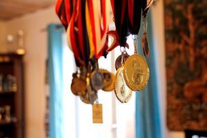 I taklampan hänger Tovas medaljer från olika sporter, och i hörnet bakom står pokalerna uppställda.
