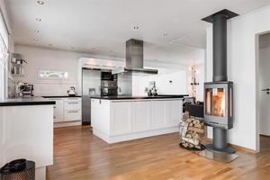 Köket är inrett i vitt - med svarta detaljer. Bild: Fastighetsbyrån