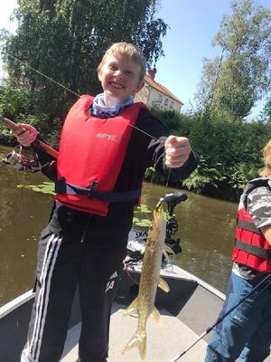Sonen har fått upp sin första gädda när han är på fiskeskola vid Skantzsjön! Lyckan är gripande! Foto: Jessica Hilller