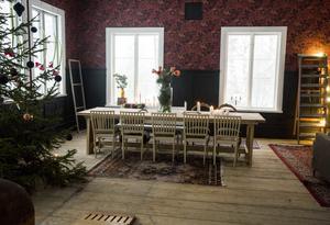Den fyra meter höga granen har Stina och Thomas huggit på den egna stora tomten, och klätt i röda och grå toner som matchar rummet.
