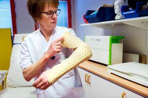 Sjuksköterskan Karin Nordin har själv aldrig behövt gå gipsad. Här visar hon på ett trägips som formats efter någon annan. Innan man lindar fast det formade trägipset får patienten ett mjukt bolster under.