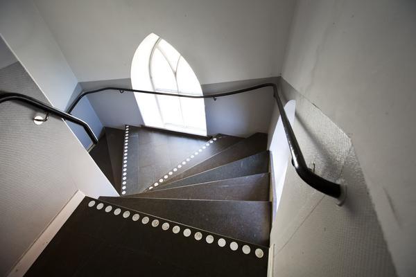 Långa trappor och spetsbågefönster.