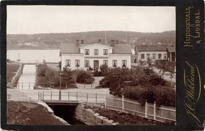 Fotografen J O Wiklund var verksam i Hudiksvall från år 1876 till 1911. Hans långa karriär sträcker sig från de tidiga första åren, då fotograferande till stora delar var ett hantverksyrke, fram till då teknikutvecklingen gjorde att det blev allt fler amatörfotografer. Även fotografen L A M Nordström hade sin ateljé i detta hus, vid Kanalparken i Hudiksvall.  Bild från Hälsinglands museum