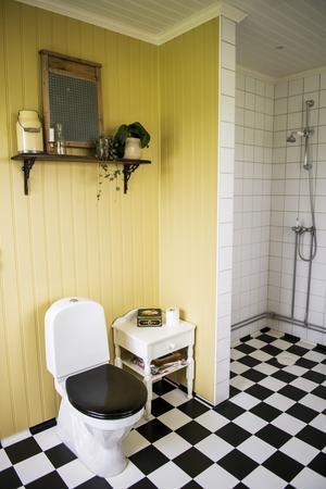 Det nyrenoverade badrummet har en vilsam känsla med schackrutigt golv, pärlspont och vitt kakel.