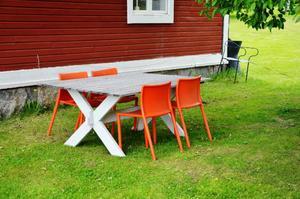 Byhuset öppnar för säsongen med nio fotografer och två konstnärer. Den orange färgen i Gerts Amanius målningar är exakt samma nyans som stolarna i trädgården.