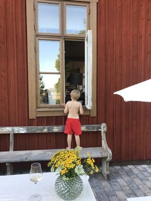 Elon 4 år beställer lite saft i fönstret i den varma sommarkvällen - här är Hedesunda Stationshus, där vi bor! Foto: Amanda Holmgren