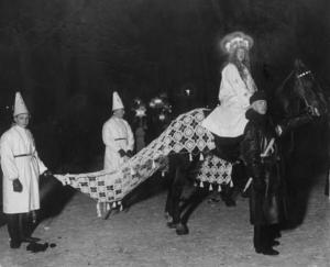 å här såg det ut när det första offentliga Luciatåget drog genom huvudstaden. Lucian kommer ridandes på en häst med ett par stjärngossar i släptåg och en poliskonstapel som myndigt håller i hästen. Året var 1927 och det var en gråkall torsdagskväll.Bild: PrB/TT