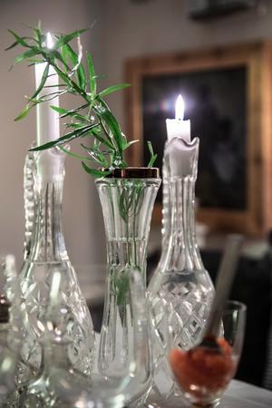 Använd glittriga kristallkaraffer till ljusstakar.  En dragonkvist förgyller bordet.