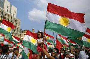 Prokurdiska demonstranter med Kurdistans röd-vit-gröna flagga med den gula solen i mitten. Foto: Hassan Ammar/AP Photo