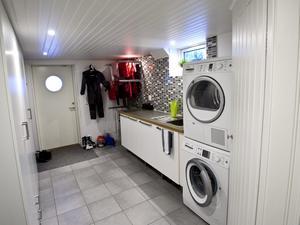 Med golvvärme och klinker har tvättstugan /groventrén blivit funktionell. Träklädda ytor gör den mer ombonad. En hel garderobsvägg gömmer kläder och prylar.