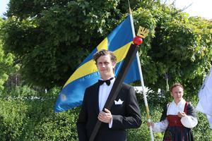 Christoffer Mannerstråle med ceremonistaven och Mikaela Håkansson med svenska flaggan redo att marschera till kyrkan.