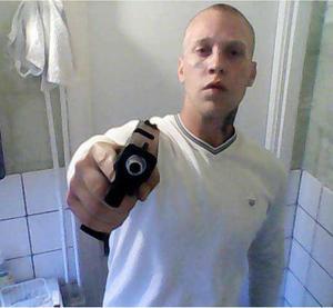 Bild ur polisens förundersökning där Rasmus Lindvall poserar med vapen.