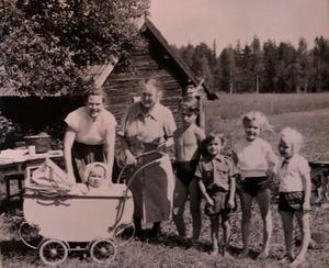 Sommaren 1956. Frida har flyttat till Lindgården och de tio brorsbarnen turas om att vara i torpet med sina familjer. Här är det familjen Helin från Västerås. Fr. vänster: Maj-Britt Helin (ogift Clason) med sonen Carl-Magnus i barnvagn, Rosina Andersson (Fridas svägerska och nybliven änka), grannbarnen Clas-Rune och Sol-Britt Lindström, Christina och Anna Karin Helin.