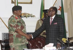 Zimbabwes president Robert Mugabe, till höger, skakar hand med general Constantino Chiwenga före talet där han berättar att han tänker avgå. Bild: AP Photo