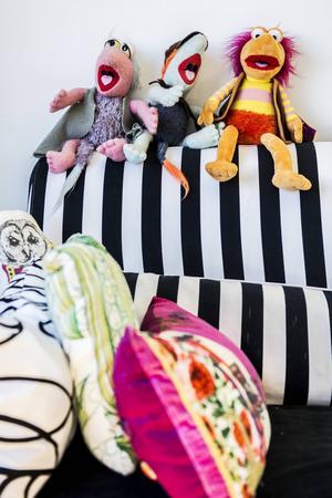 Ett minne från barndomens tv-program sitter uppradade på soffkanten. Två av dem hade hon själv som barn och en har hon fått i present.