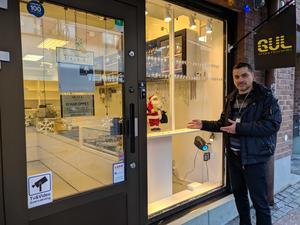Ayar Fadhil utanför sin guldsmedsbutik på Storgatan. I väntan på nytt ytterglas kommer ett skydd att sättas upp. Kvar finns den närmast okrossbara innerrutan.