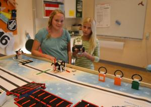 Maja Holmström och Agnes Wicander visar den robot som robotgruppen byggt av Lego och som man ska tävla med på lördag i First Lego League i Borlänge.