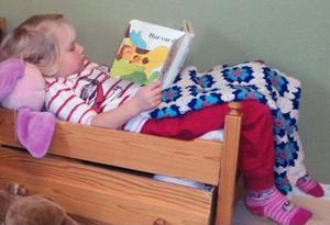 En bild från en av Moras förskolor, där ett barn är i full färd med att läsa en bok som kommit i en sändning från biblioteket i Mora.