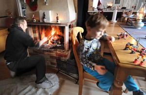 Lars-Göran Forsberg eldar för att hålla värmen medan Viggo leker vid bordet.
