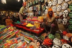En försäljare säljer färgpulver och masker under festivalen.