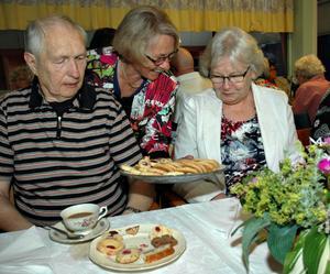 Birgitta Larsson bjuder Tjelvar och Karin Wesström på syltgrottor och havrekakor.
