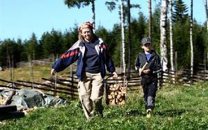 Annette Westberg från Enköpingmed sonen Erik praktiserar en vecka genom Naturskyddsföreningen hos Yvonne och Ove på Kättboåsens fäbod.– Vi har det jättebra här, och Erik tycker det är jätteroligt att fixa med hönsen. säger Annette och njuter i solskenet. Foto: Bons Nisse Andersson