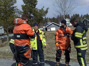 Räddningstjänstpersonal byter om för att i en slags flotte ge sig ut på isen.
