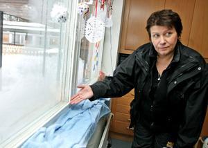Skyddsombud Karin Syrén lägger nya handdukar vid fönstret för att få bort den värsta vätan.