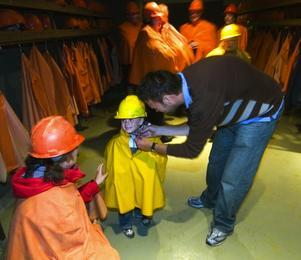 Det gäller att skydda både kropp och knopp när man ska ner i gruvan. Linda och Tommy Lundberg hjälper sonen Ivar på med hjälm och cape. Foto:Mikael Forslund