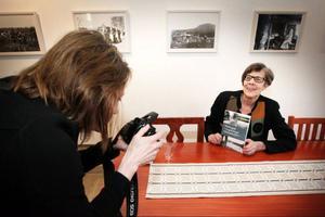 Jamtlis biträdande museichef Charina Knutson förevigar författardebuterande Karin Preusler som kom till Jamtlis kafé för att fira att hennes bok om Ytterhogdal nu är släppt.