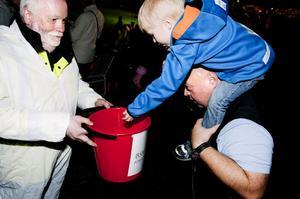 Treåriga Victor Nordin och hans pappa Peter var inte sena att lägga en slant i Bengt Perssons kollekthink.