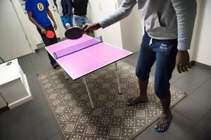 Flyktingar försöker få tiden att gå på asylboendet med en bordtennismatch.